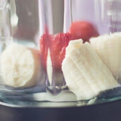 Pieces of strawberry and banana in a blender, ready to be blend together